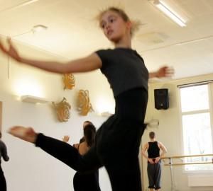 Dansare mitt i ett hopp, höger hand ut från kroppen, vänster ben böjt bakåt.