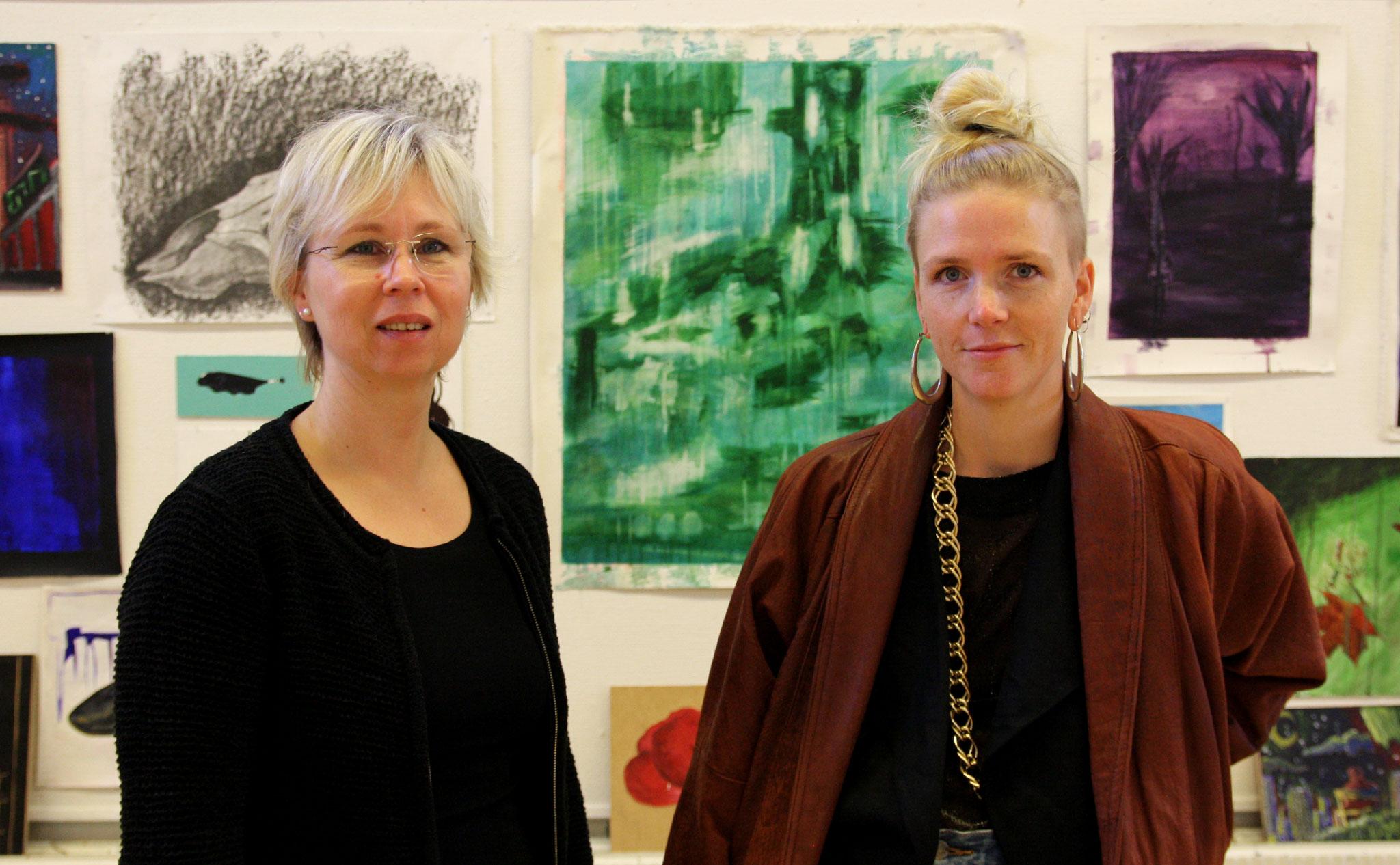 Maria Bygdén t.v. och Ellinor Augustini t.h. i halvbild. Bakom dem en vägg full av tavlor.