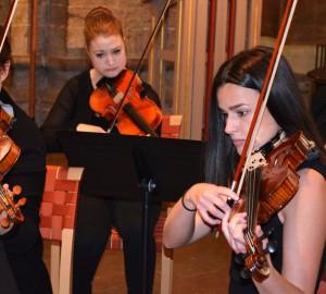 Stråkensemble med fyra fiolspelare. En i förgrunden och fokus, övriga i bakgrunden.