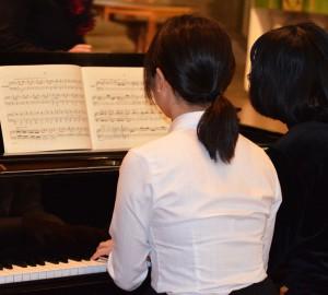 Två pianister vid ett piano. Ena i vit blus, andra i svart tröja.