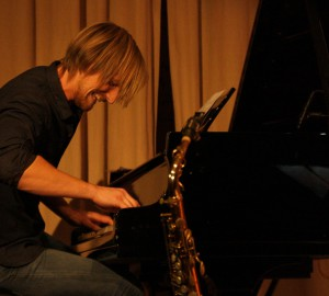Pianist som lutar sig fram över klaviaturen och spelar intensivt.