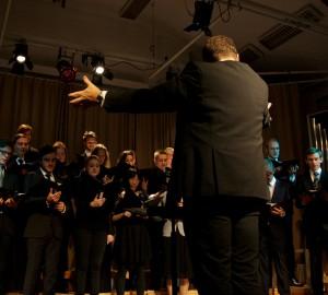 Kör och dirigent sett snett från sidan. Dirigenten med ena armen höjd.