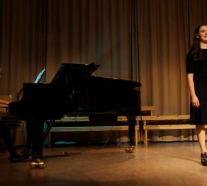 Pianist till vänster sitter vid en flygel. Sångerska till höger.