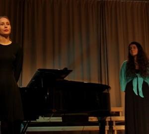 En duo, pianisten står upp och presenterar stycket dom ska spela. Sångerska i bakgrunden.