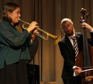 Jazzensemble, en person spelar trumpet i förgrunden. I bakgrunden spelar en person ståbas med stråke.