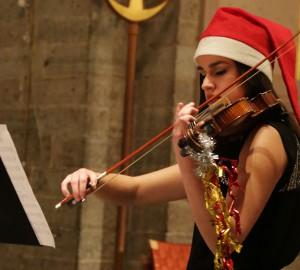 Fiolspelare med tomteluva och juldekorationer på fiolen.