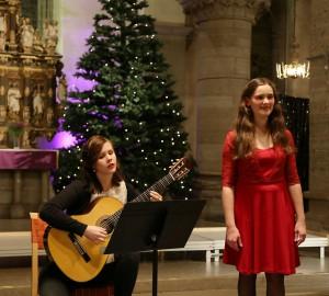 Duo med klassisk gitarr och sång. I bakgrunden en julgran och kyrkovalv.