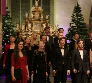 En del av skolans kör. I bakgrunden en julgran och stora kyrkofönster.