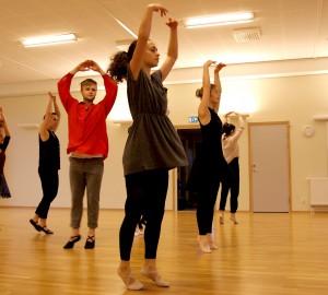 Dansare i balettskor. Står på tårna med armarna ovanför huvudet, bildar en cirkel.