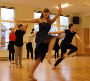 En grupp dansare. En av dem mitt i ett utfall med högt knä, tittar mot kameran