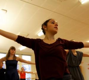 En dansare i halvfigur nära kameran, armarna utsträckta åt sidorna, huvudet vänt åt höger.