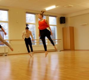 Fyra dansare mitt i ett synkroniserat hopp.