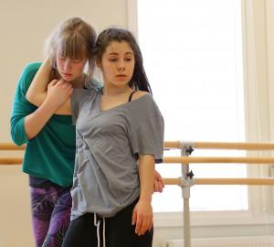 En dansare omfamnar en annans huvud. Står snett bredvid varandra.