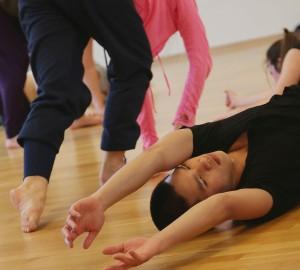 En dansare ligger på rygg på golvet. Hela överkroppen och armarna utsträckta snett nedåt mot kameran.