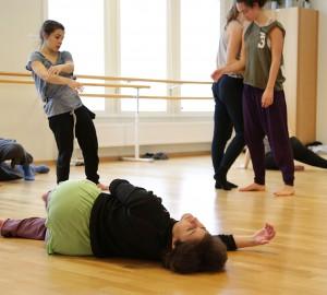 Flera dansare på golvet. Tre stående. En av de liggande, på sidan, är Hagit Yakira som leder workshopen.