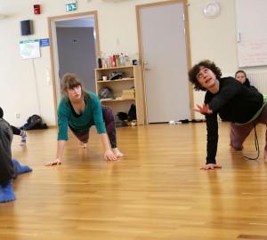 Hagit Yakira instruerar danseleverna. Står på ett knä, med en hand i marken. Andra handen utsträckt framför sig. Huvudet vänt och tittar uppåt mot taket.