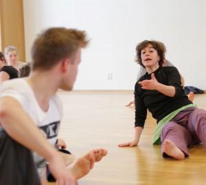 Hagit Yakira sitter på golvet och instruerar eleverna. En elev nära kameran men vänd bakåt, tittar mot Hagit.