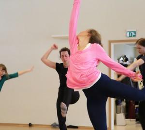 Flera dansare i fartfylld rörelse. Närmast kameran Isabell Gisselgård - en arm sträckt rakt upp, ena benet sparkar bakåt. Huvudet vinklat över ena axeln.