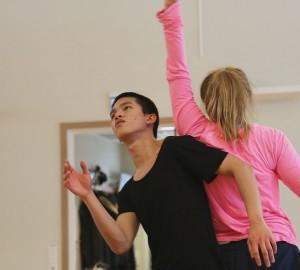 Två dansare med ryggen mot varandra. En med ansiktet mot kameran, tittar snett upp i taket. Den andra armen lyft rakt upp i luften.
