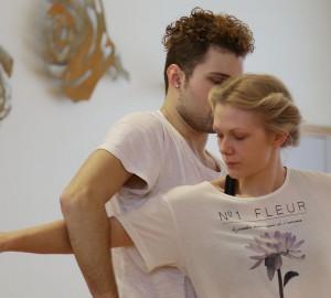 En dansare sträcker sin arm igenom bågen som en annan dansares arm bildar.