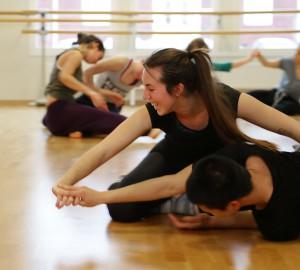Två dansare på golvet. Den ena ligger, den andra på knä bakom. De drar varandra framåt i händerna.