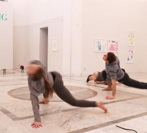 Två dansare med en hand och två fötter i golvet. Dom böjer kroppen uppåt. Det går fort, bilden är suddig.