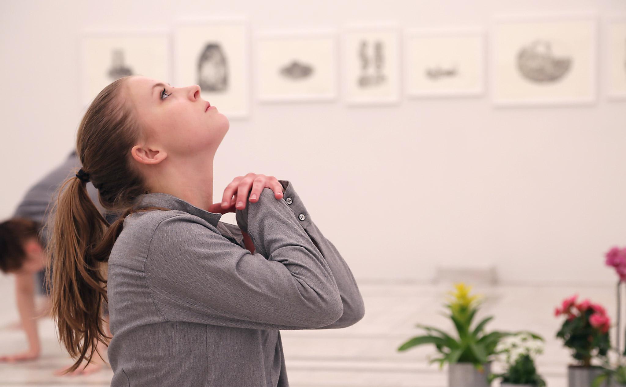 En dansare sitter på golvet och tittar upp i taket. Händerna nästan i en bön under hakan.