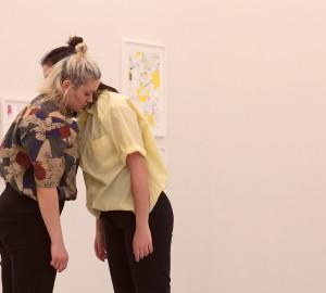 Två dansare som lutat sig ansikte mot ansikte mot varandra. Armarna slappa längs sidorna.