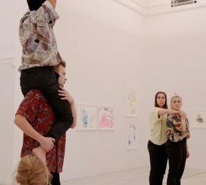 Fem dansare i två grupper. En sitter på en annans axlar och sträcker händerna uppåt. Två står längre bak i bilden och tittar på det mänskliga tornet.
