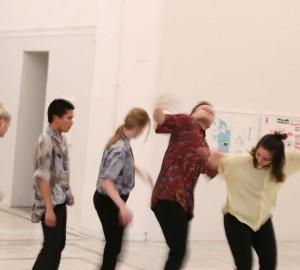 Fem dansare står på rad horisontellt över bilden. De skakar ryckigt med sina kroppar.