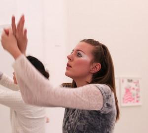 Nära foto på en dansares ansikte och armar. Med blicken på händerna gör hon en sorts fågelimitation, en flaxande rörelse med händerna.