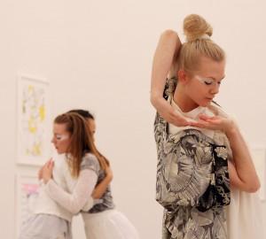 I förgrunden en dansare som fattar sina båda händer, ena armen bakom huvudet och ner mot motsatt axel. I bakgrunden två dansare i en omfamning.