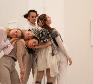 Flera dansare i horisontell rad, vilar sina huvuden på varandras axlar och ryggar.