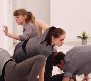 Fyra dansare på golvet. En är på väg upp. I förgrunden en svart elsladd.