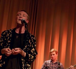 En deltagare sjunger, blicken riktad uppåt och bårtåt. I bakgrunden en basist.