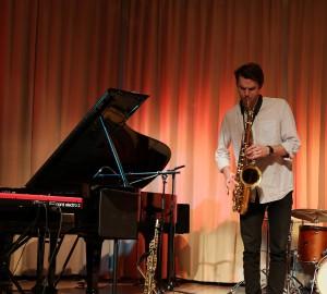 Saxofonist spelar solo. Till vänster en deltagare på keyboard och i bakgrunden en trummis.