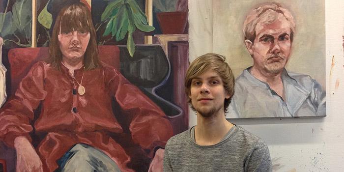Portärttbild av Johan Wiman, med två tavlor i bakgrunden.