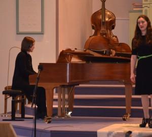 Sångare som kompas på piano.