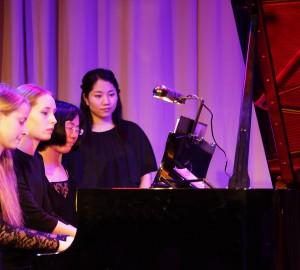 Tre pianister spelar samtidigt på en flygel.