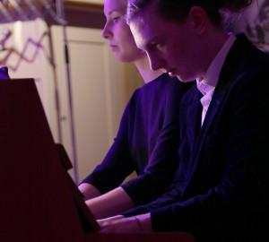 Två pianister spelar fyrhänt piano.