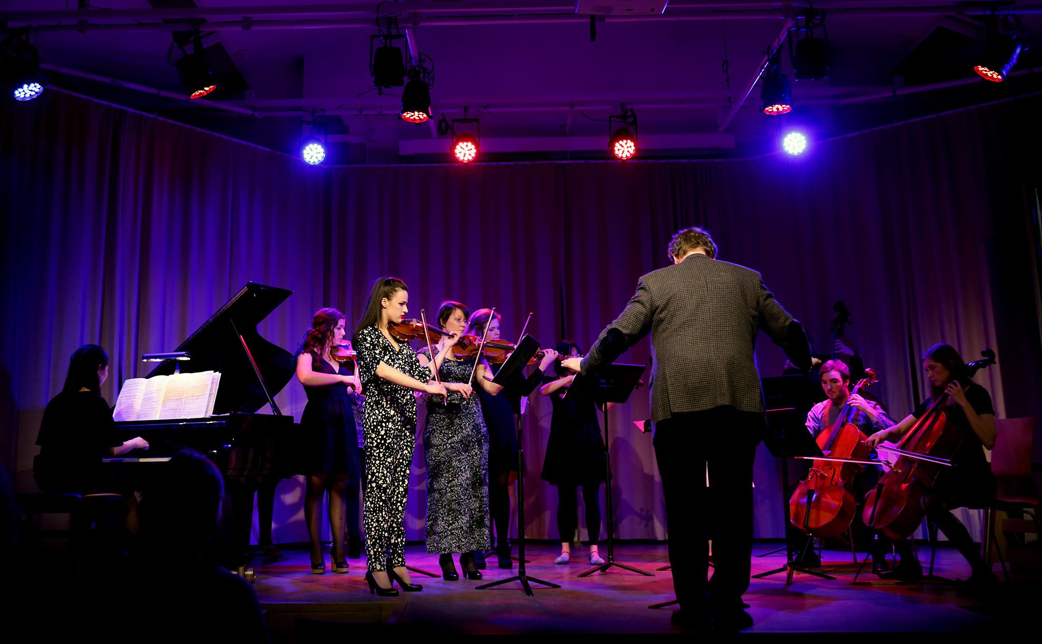 Orkester med elva deltagare. I förgrunden en dirigent. Till vänster solo-pianist.