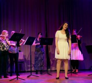 Sångerska framför en större klassisk ensemble med stråk och blås.