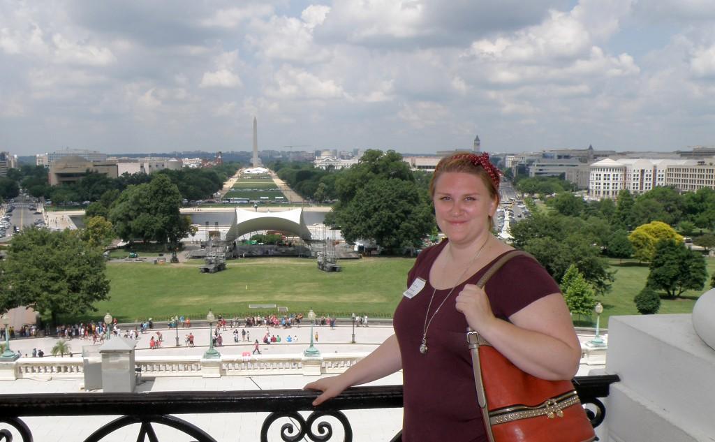 Liljan framför ett räcke med utsikt över Washingtonmonumentet.