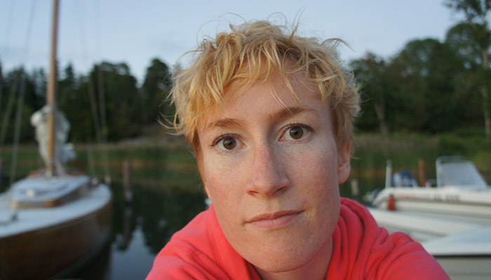 Porträttbild av Linnea Lindholm. I bakgrunden segelbåtar.