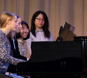 Tre deltagare från musiklinjens klassiska inriktning spelar sexhänt piano.