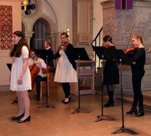 En kammarmusikensemble med sångare, fyra stråkar och en orgel.