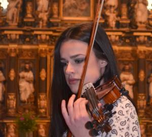 Närbild på en tjej med fiol. I bakgrunden en altartavla.