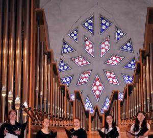 Fem sångare på en balkong i Nicolaikyrkan. I bakgrunden orgelpipor.
