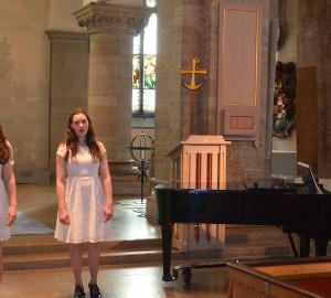 Till vänster två sångare och till höger en pianist.