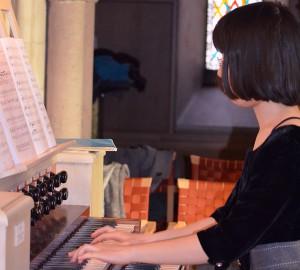 Orgelspelare. I bakgrunden ett färgglatt fönster.